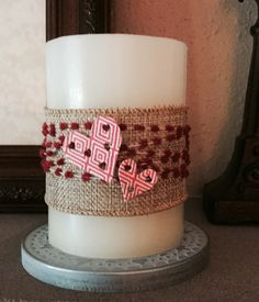 Quickly turn a simple candle into a Valentine's decoration with some burlap ribbon, string and hearts.  (Hearts were cut using Sizzix Heart card die).
