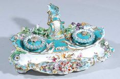 A 19th century Coalport porcelain inkstand, with encrusted flowers over a teal blue ground, fitted with a pair of inkwells and covers and a pen rest, painted with cut blooms, 21cm (8 1/4in) wide