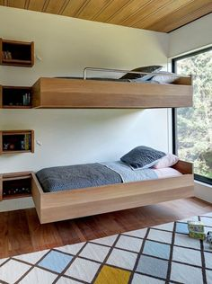 13 Exceptional Examples Of Bunk Beds To Inspire You // These beds are a great example of cantilevered bunk beds. The built-in wall shelves also double as foot holes for climbing to the top bed.