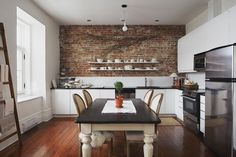 Mix of modern cabinetry with rustic exposed brick and hardwood flooring.