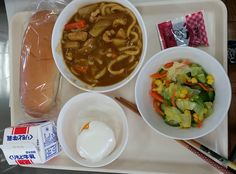 Kyushoku with vegetables, curry soup and crackers, bun, peach with yogurt, and milk