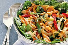 A skillet stir-fry made with chicken, veggies and peanuts is served over salad greens to make this quick and easy Asian-inspired dish.