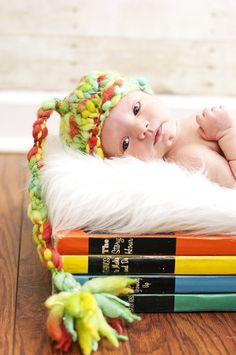 Newborn photo idea. Stack of vintage books with colorful crochet hat.
