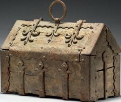 BOX saddle oak and wrought iron H: 16 cm - W: 24.5 cm - D: 11.5 cm thirteenth century Style Light accidents and gaps in oak cask, this box is built in the form of hunting with a hinged lid half slope. It is encircled by lilies hinges on all sides. At the corners, angles reinforcements cut, above a gripping ring and on the side, a lock case with a lock. The hasp is missing