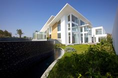 Architecture, White And Light Brown Exterior Modern House Design With Sloping Roof And Garden Plus Small Pond Ideas: The Luxurious Contemporary Residence Bahrain House Architected by MORIQ