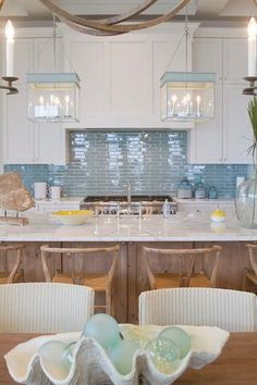 Cottage kitchen features a pair of turquoise lanterns, The Urban Electric Co Chisholm, over a stained center island topped with white marble fitted with a sink and deck mount faucet lined with hans Wegner Wishbone Barstools.