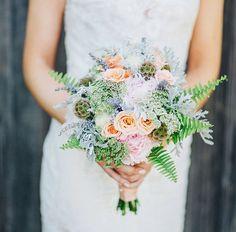 Coquet et fin, ce bouquet de petites roses orangées, agrémenté de verdure claire, entouré de fougères, apporte un concentré de délicatesse par sa finesse et la volupté de ses teintes.