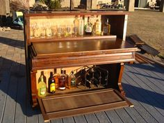 """Repurposed piano full bar and cabinet. source: bendmortgagelender.com  Repurposed piano full bar and cabinet (top photo): an old 1896 piano was gutted but is now filled with the """"spirits"""" of music. When the cabinet doors are closed this literal piano bar still looks like a piano. Extra cool factor? There is room under the the keyboard cover for shot glasses and stir sticks."""