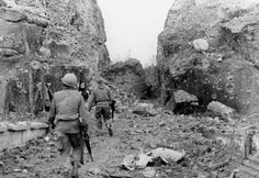 During the battle for Hue,US troops move through an area scarred from heavy artillery fire.
