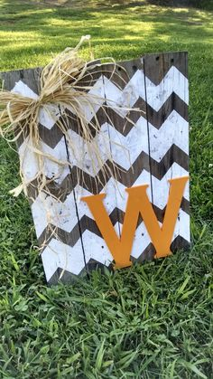 DIY Idea: Chevron painted pallet with family initial. Replace the raffia with a burlap bow.