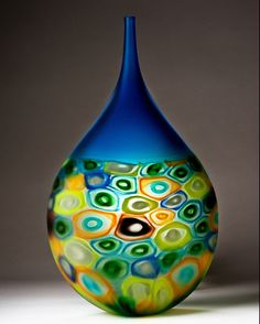 Aquis by Chris McCarthy. *Blown glass* bottle with a mix of colorful *murrini* and an aquamarine top. *Sandcarved:carved glass* and acid finished.