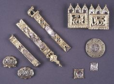 Three plaques for a belt; silver-gilt; shaped, with a central roundel enclosing a white filigree enamel flower against a brown enamel ground; smaller flower each side; textile fragments adhere to reverse.