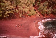 Red Sand Beach (also known as Kaihalulu) is located in Maui, Hawaii and is a pocked beach, partially isolated from the ocean. Because this area is rich in iron, the sand has a red-black color which makes a great contrast with the water.
