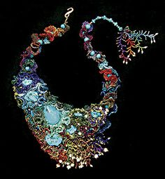 "Mary Darwall, First Place  Pendants/Necklaces  Eleven turquoise cabochons, turquoise beads, freshwater pearls, glass seed beads,   beading cloth, nylon thread, 49-strand wire, 14K closure, leather backing. Hand   needle woven, bead appliqué, freeform peyote, branching stitches. 18"".     Photo: John Yohman.  www.marydarwall.com"