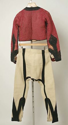 Ensemble Date: late 19th–early 20th century Culture: Albanian Medium: wool, silk, cotton, leather, metal Dimensions: Length at CB (a): 15 1/2 in. (39.4 cm) Length at CB (b): 15 1/2 in. (39.4 cm) Length at CB (c): 37 in. (94 cm) Length at Side Seam (d): 38 in. (96.5 cm) Length (e): 99 1/4 in. (252.1 cm) Length (f, g): 12 1/4 in. (31.1 cm) Length (h): 13 1/2 in. (34.3 cm) Length (i): 34 1/2 in. (87.6 cm) Credit Line: Gift of Burta May Taylor in memory of her husband, Elliot J. Taylor, 1988…
