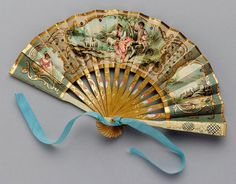 vicfangirlguide:    A miniature fan from the 1880s designed as a wedding favour for a bridesmaid. This fan was a mass-produced lithograph design, printed onto paper leaf, with gilded highlights, small metal sequins and painted wooden sticks. Lithographed fans such as this were extremely popular from the 1840s onwards and commonly depicted romantic 18th century pastoral scenes.