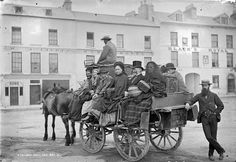 A mail car near Black's Royal Hotel, Eyre Square in Galway city, Ireland, loaded with a great mix of passengers, c. 1880.