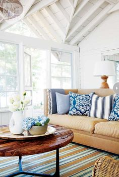 Coastal living room, white walls, blue and white textiles and lots of natural light.