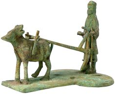 Ancient Sumerian Bronze ceremonial statue of a standing male farmer behind a single ox plowing a field, the surface of the base covered in incised flora design. Green patina. 2000 BC