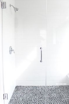 Gray and white bathroom ideas. Spa-like rock flooring that warms up in the shower to comfort tired feet! Pebble Shower Floor, White Subway Tile Shower, White Bathroom Tiles, Bathroom Flooring, Small Bathroom, Large Tile Shower, Gray And White Bathroom Ideas, Subway Tile Showers, White Shower