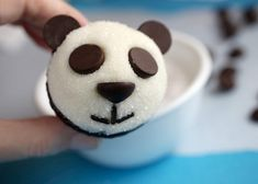 Little panda faces on mini cupcakes using chocolate chips, could use Enjoy Life Foods nut free and vegan chips!  The white part is frosting dipped in sugar which I think is doable too!