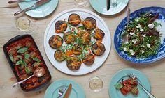 A table laid with dishes of aubergine and almond cakes; aubergine wedge salad with pine nuts and ricotta; and aubergine polpette.