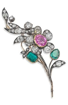 An antique gem-set spray brooch, 19th century. Of flower spray design, the flowerhead set with an oval-cut pink sapphire to petals set with old cushion-cut diamonds, the leaves set with mixed-cut emeralds, old cushion and old round brilliant-cut diamonds, converts into a hair ornament, length 80mm.
