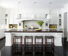 The dark counter top and dark stools warm up the space.  The judicious use of glass fronts break up the line of white.  I like the symmetry of the pendants.