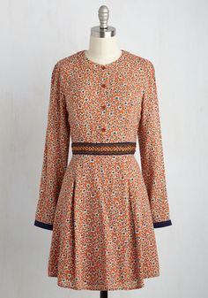 Strolling to the coffee shop in this orange dress, you keep your order in mind - a brew as robust as your ensemble! The barista and your besties both savor the long sleeves, navy braided waistline, and box pleats of your retro floral frock, which prompts a toast to your style all around the cafe.