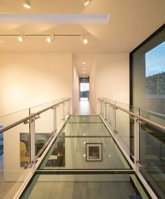 In this modern house, there's a glass bridge that crosses the art gallery and connects the living areas with the bedrooms. #GlassBridge #Architecture #GlassWalkway