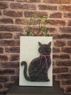 Un petit chat noir avec son collier rose brillant, réalisée avec la technique du string art ou encore du fil tendu. Il est sur un support en bois teinté blanc de taille 20/30 des pointes en acier poli et du fil pour crochet noir et rose argenté