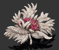 VAN CLEEF & ARPELS - Années 1950   Magnifique clip « Dalhia » en platine, le feuillage dentelé est entièrement pavé de diamants. La fleur de dalhia est représentée par des rubis cabochons ovales montés en chatons à griffes. La tige est sertie de diamants baguette.   Système clip à double épingles en or. Travail français signé Van Cleef & Arpels et numéroté. Poids brut : 65,5 gr. Hauteur : 6,1 cm Largeur : 8 cm environ
