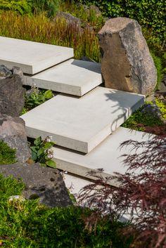 Zwevende trap in tuin met veel hoogteverschil.