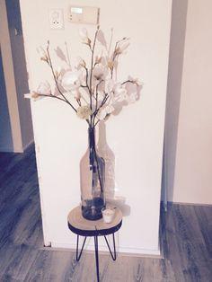 Kunstbloemen decoratie in hoge vaas op bijzettafel. Faux flowers decoration on a side table