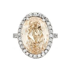 Magnificent 10.34 Carat Champagne Diamond Solitaire Ring. Set with an oval brilliant-cut champagne colored diamond, weighing 10.34 carats, within a brilliant-cut white diamond surround and shoulders, mounted in platinum, c2013