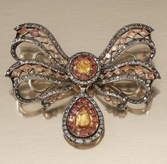 TOPAZ AND DIAMOND DEVANT DE CORSAGE, PORTUGUESE SECOND HALF OF THE 18TH CENTURY. Designed as a stylised open work tied ribbon bow, centring on a circular cluster, suspending a pear-shaped drop, set with foil backed mixed-cut topaz, table- and rose-cut diamonds, detachable drop.