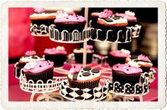 A dessert table would feature an assortment of black, white, and pink cupcakes displayed on various metal trees and ceramic cake stands