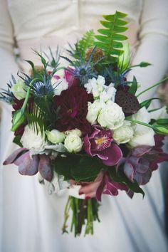 Ein eleganter Brautstrauss mit weißen und purpur-farbenen Blüten und Distel