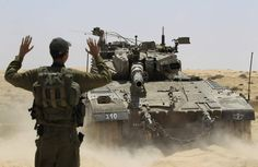 An Israeli soldier directs a tank, maneuvering near the border between Israel and Egypt