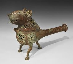 """Islamic Bronze Openwork Lion Incense Burner. 18th century AD or earlier. A cast openwork zoomorphic vessel with three legs, openwork panels to the shoulders and chest, separate hinged head casting with openwork panels to the neck; to the rear a substantial round-section handle with rosette finial. 3.4 kg, 42 cm (16 3/8""""). Property of a London gentleman; acquired 1985-1995."""
