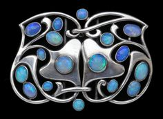 An exceptional Art Nouveau foliate silver buckle by Murrle Bennett & Co set with an abundant selection of beautiful opals. Tadema Gallery