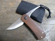 This is a newly handmade friction folder. The blade is 1095 steel that is convex ground, given a satin finish, and differentially tempered. The blade pivot is hand made from stainless steel tubing. The handle is made of mahogany that has been given an oil finish. The paracord tail can