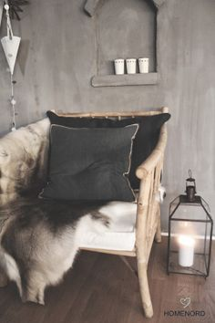 TINE K BAMBU - gorgeous armchair layered with warming blankets and cushions.