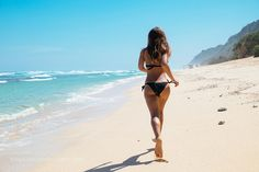 Woman running through sea water on a beach in Bali. Female runner jogging during outdoor workout... by ca2600