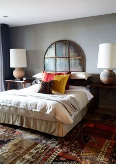 antiqued mirror as headboard, multi-layered rugs, and subtle gray walls -- ontwolanesof-freedom.tumblr.com