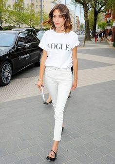 "Alexa Chung wears a white ""Vogue"" t-shirt, white jeans, and black patent leather flats"