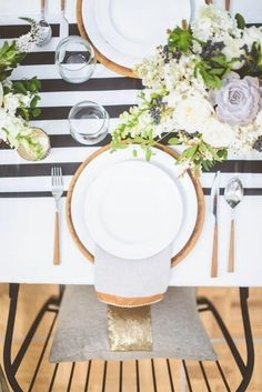 Black and white striped wedding table runner on a rustic table setting with white floral centerpieces.