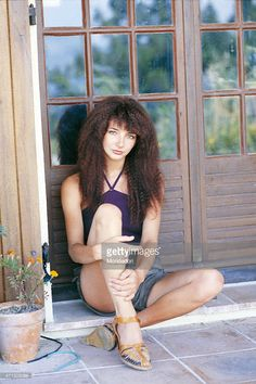 The British singer Kate Bush, sitting on the floor, leaning against a door in glass and wood, posing for a photo shoot. Italy 1978