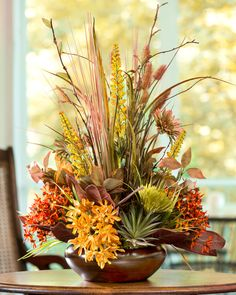 """Autumn branches and grasses stand tall, flanked by vibrant orange tones of silk Agapanthus and Kopsia in this bountiful autumn design. Permanent succulents and autumn silk foliage provide added texture and dimension. Arranged in a 10"""" round antique bronze fiberglass bowl, it's a wonderful display on any table top in the home and office."""