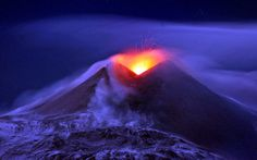 Molten lava erupts from the volcano of Mount Etna during a snow storm on the Italian island of Sicily